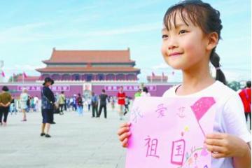 """小學生用畫筆書寫""""我愛您,祖國!"""""""